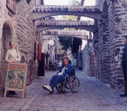 Nancy travels Estonia> It's a bumpy ride in her wheelchair becauseof the brick roads but she loves every minute of it.